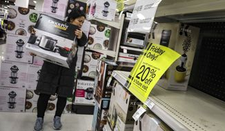 A shopper carries a crockpot during Target's Black Friday sale, in the Borough of New York. The National Retail Federation, the nation's largest retail group,  expects that holiday sales could actually exceed growth seen in prior seasons despite the uncertainty surrounding the pandemic. (AP Photo/Bebeto Matthews, File)