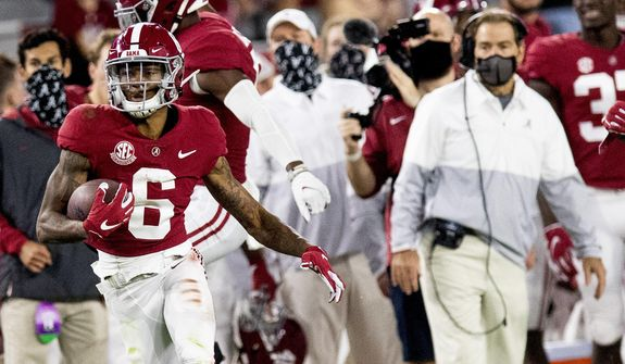 Alabama wide receiver DeVonta Smith (6) heads for a long gain as coach Nick Saban watches during the team's NCAA college football game against Kentucky on Saturday, Nov. 21, 2020, in Tuscaloosa, Ala. (Mickey Welsh/The Montgomery Advertiser via AP) **FILE**