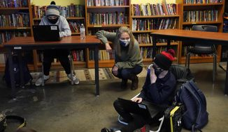 Susannah Remillard, middle, speaks to one of her sixth-grade students at Cape Cod Lighthouse Charter School, Thursday, Nov. 19, 2020, in East Harwich, Mass. In a growing number of U.S. schools, students are now learning a more complex Thanksgiving story that involves conflict, injustice and a new focus on the native people who lived in New England for hundreds of years before European settlers arrived. (AP Photo/Elise Amendola)