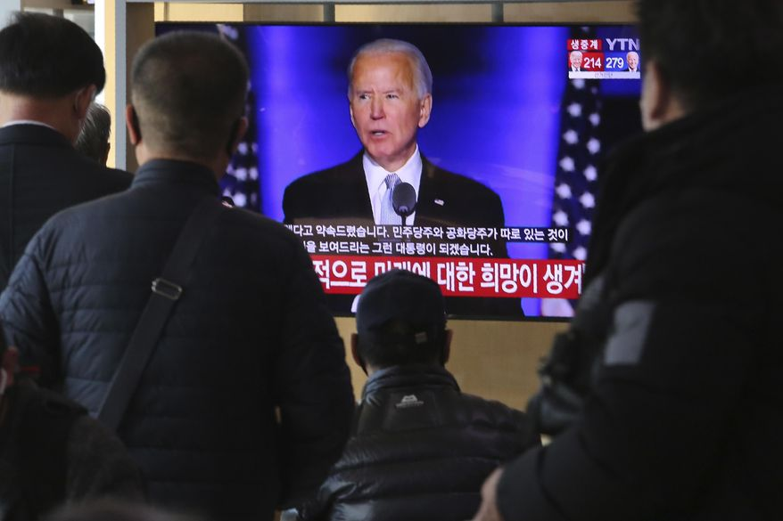 FILE - In this Nov. 8, 2020, file photo people watch a TV screen showing the live-broadcast of President-elect Joe Biden speaking, at the Seoul Railway Station in Seoul, South Korea. (AP Photo/Ahn Young-joon, File)