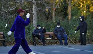 People wearing face masks to help curb the spread of the coronavirus chat each other as a man performs morning exercise at a park in Beijing, Monday, Nov. 23, 2020. (AP Photo/Andy Wong)