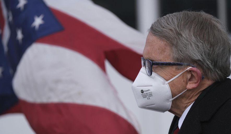Ohio Gov. Mike DeWine looks on during a press conference Wednesday, Nov. 18, at Toledo Express Airport in Swanton, Ohio. On Tuesday DeWine announced a three-week 10 p.m. to 5 a.m. general curfew, with multiple exceptions, meant to slow the spread of the coronavirus as cases stay at near-record high levels. (J.D. Pooley/Sentinel-Tribune via AP)