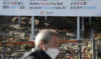 A man wearing a face mask walks past a banner showing precautions against the coronavirus in Seoul, South Korea, Monday, Nov. 23, 2020. (AP Photo/Lee Jin-man)