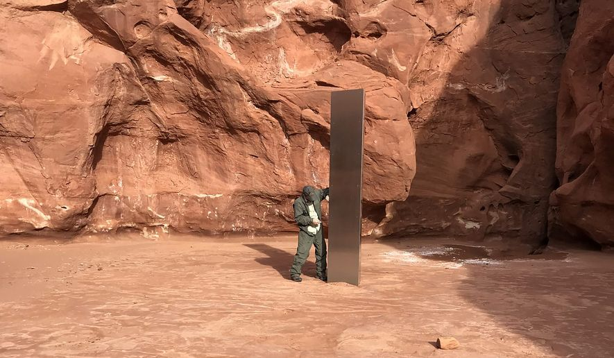 This Nov. 18, 2020 photo provided by the Utah Department of Public Safety shows a Utah state worker inspecting a metal monolith that was found installed in the ground in a remote area of red rock in Utah. The smooth, tall structure was found during a helicopter survey of bighorn sheep in southeastern Utah, officials said Monday. State workers from the Utah Department of Public Safety and Division of Wildlife Resources spotted the gleaming object from the air and landed nearby to check it out. The exact location is so remote that officials are not revealing it publicly, worried that people might get lost or stranded trying to find it and need to be rescued. (Utah Department of Public Safety via AP)