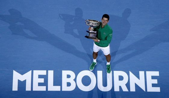 """In this Feb. 3, 2020, file photo, Serbia's Novak Djokovic holds the Norman Brookes Challenge Cup after defeating Austria's Dominic Thiem in the men's singles final of the Australian Open tennis championship in Melbourne, Australia. The political leader of Australia's Victorian state says Wednesday, Nov. 18, 2020, despite """"incredibly complex"""" negotiations, he is confident January's Australian Open tennis tournament will proceed. (AP Photo/Andy Wong) **FILE**"""