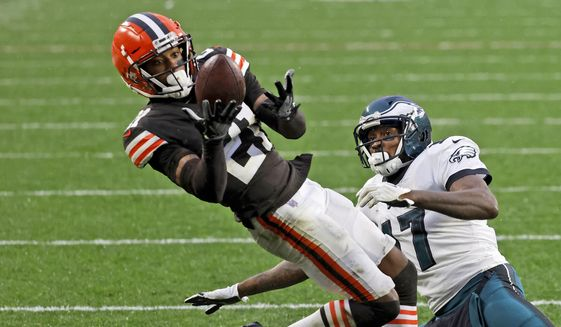 FILE - In this Sunday, Nov. 22, 2020, file photo, Cleveland Browns cornerback Denzel Ward (21) intercepts a pass intended for Philadelphia Eagles wide receiver Alshon Jeffery (17) during an NFL football game in Cleveland. Ward is expected to miss at least a few games with a calf injury sustained in Sunday's win over Philadelphia. Ward, who had an interception and several pass breakups, underwent an MRI on Monday, Nov. 23, 2020. (AP Photo/Kirk Irwin, File)