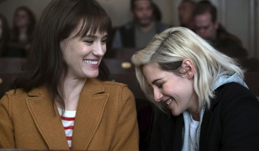 "This image released by Hulu shows Mackenzie Davis, left, and Kristen Stewart in a scene from ""Happiest Season."" (Hulu via AP)"