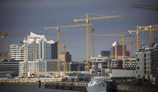 Construction cranes are located at various construction sites at Bakenhafen and Ueberseequartier in Hafencity in Hamburg, Germany, Monday, Nov. 16, 2020. In the background you can see the striking roof silhouette of the Elbe Philharmonic Hall. (Christian Charisius/dpa via AP)