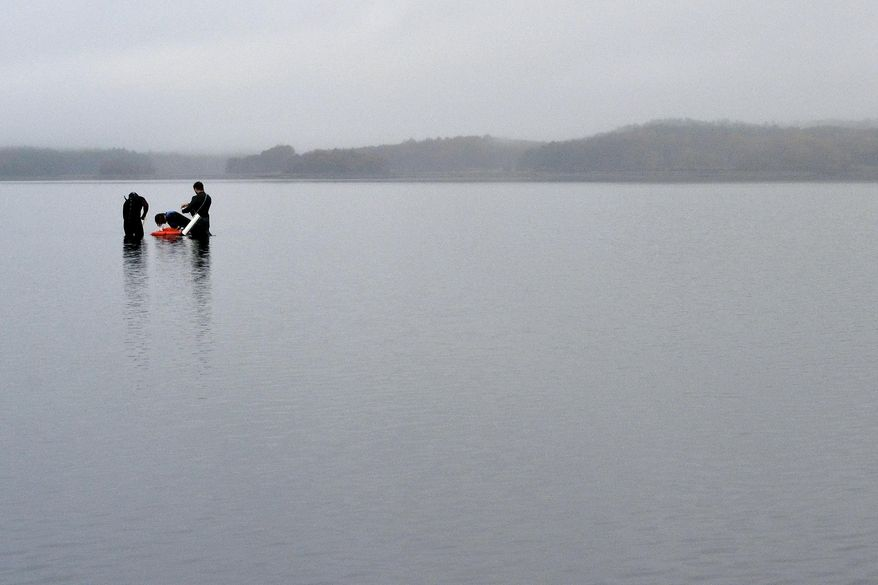 FILE - In this Oct. 29, 2019, file photo, University of New Hampshire scientists monitor the health of seagrass in the Great Bay in Durham, N.H. Federal officials have finalized a plan in November 2020 to reduce pollution in one of the largest estuaries in the Northeast. (AP Photo/Michael Casey, File)