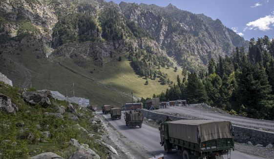 FILE - In this Sept. 9, 2020, file photo, an Indian army convoy moves on the Srinagar- Ladakh highway at Gagangeer, northeast of Srinagar, Indian-controlled Kashmir. India banned 43 mobile apps on Tuesday in a move targeted at China, with which it is locked in a military standoff along a border in the Himalayas.(AP Photo/ Dar Yasin, File)