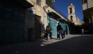 Palestinians walk past closed stores near the Church of the Nativity, traditionally believed by Christians to be the birthplace of Jesus Christ, in the West Bank City of Bethlehem, Monday, Nov. 23, 2020. The Palestinian economy is expected to contract by about 8% in 2020 as it copes with the effects of the coronavirus pandemic, an already struggling economy and political standoff with Israel, the World Bank said in a report Tuesday, Nov 24, 2020. (AP Photo/Majdi Mohammed)
