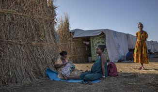 """Ethiopian Amhara refugee 8-month pregnant Blaines Alfao Eileen, right, sits with Tigray refugee 25-year-old Lemlem Haylo Rada, holding her one-month old baby who was born on a street as she fled, at Um Rakuba refugee camp in Qadarif, eastern Sudan, Monday, Nov. 23, 2020. Ethiopia's government is again warning residents of the besieged capital of the embattled Tigray region as the clock ticks on a 72-hour ultimatum before a military assault, saying """"anything can happen."""" (AP Photo/Nariman El-Mofty)"""
