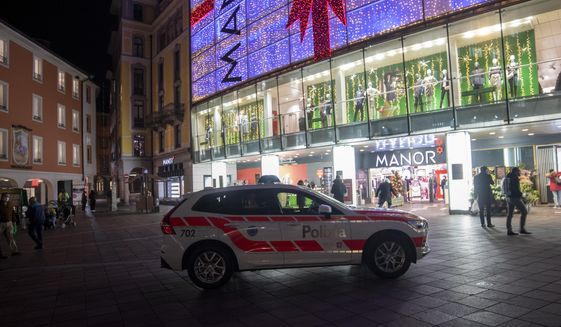 A police car in the area where a stabbing occurred in the department store, in Lugano, Switzerland, Tuesday, Nov. 24, 2020. Swiss authorities are investigating as a possible terror attack the stabbing of two women in an department store in the southern city of Lugano, and a suspect has been arrested. Officials said one of the victims sustained serious but not life-threatening injuries, while the other sustained minor injuries. (Ti-Press/Keystone via AP)