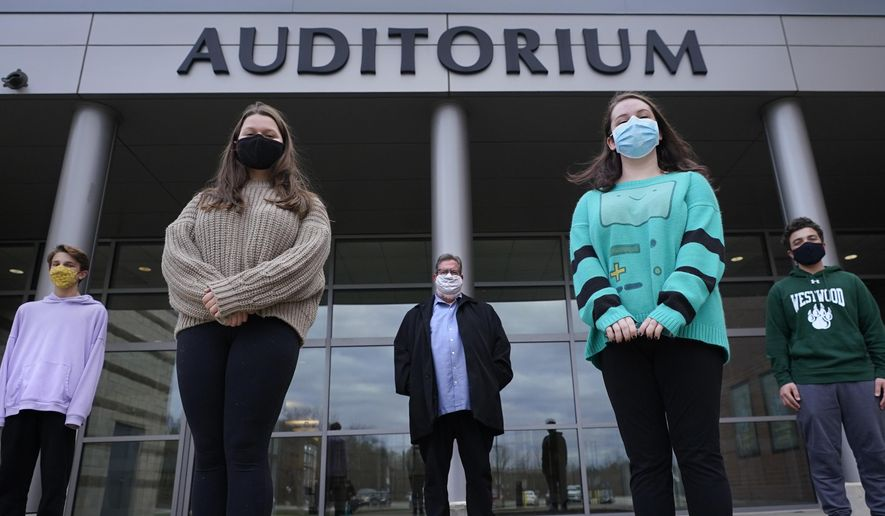 "While wearing protective masks due to the COVID-19 outbreak, Jim Howard, a drama teacher at Westwood, Mass., High School, center, poses with his student actors outside the school's auditorium after working on their virtual performance of Shakespeare's ""Romeo and Juliet,"" Monday, Nov. 16, 2020, in Westwood. The production, which would usually be presented onstage, shifted to a virtual audience due to the pandemic. From left are Ryan Kaplan, who portrays the friar, Lucy Vitali, who portrays Juliet, Howard, Cassidy Hall, who portrays the nurse, and Alex Mansour, who portrays Romeo. (AP Photo/Charles Krupa)"
