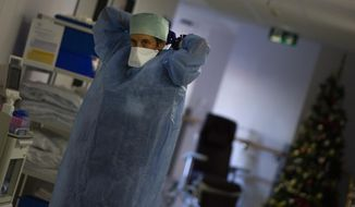 A Belgian Army medic suits up as she prepares to deliver lunch to patients with COVID-19 at the St. Michiel Hospital in Brussels, Tuesday, Nov. 24, 2020. The Belgian military has been called into several hospitals and care homes to alleviate the stress on healthcare personnel. (AP Photo/Virginia Mayo)