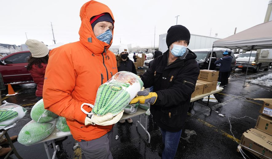 "Chad MacKenzie, right, hands a frozen turkey to Mike Brumbaugh, both volunteers from Vail, Colo., to give to a motorist as part of a ""Banquet in a Box"" from the Denver Rescue Mission as the Thanksgiving Day feasts are distributed in a parking lot at Empower Field at Mile High early Tuesday, Nov. 24, 2020, in Denver. More than 3,000 of the boxes filled with the ingredients for a traditional Thanksgiving dinner were handed out through the rescue mission and the Denver Broncos. (AP Photo/David Zalubowski)"