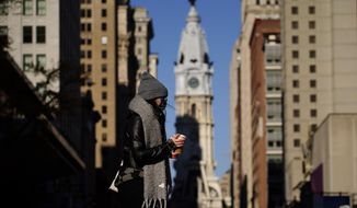 In this Nov. 18, 2020 photo, a person wearing a face mask crosses Broad Street in Philadelphia. As governors and mayors grapple with an out-of-control pandemic, they are ratcheting up mask mandates and imposing restrictions on small indoor gatherings, which have been blamed for accelerating the spread of the coronavirus. (AP Photo/Matt Slocum)