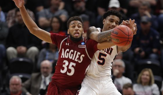 FILE - In this Thursday, March 21, 2019, file photo, New Mexico State forward Johnny McCants (35) and Auburn forward Chuma Okeke (5) battle for the ball in the first half during a first round men's college basketball game in the NCAA Tournament in Salt Lake City. Coronavirus restrictions in New Mexico make it impossible for the schools there to play their seasons. McCants and his New Mexico State teammates have settled into a regular routine less than a week after the team temporarily relocated to Phoenix, amid the pandemic. (AP Photo/Jeff Swinger, File)