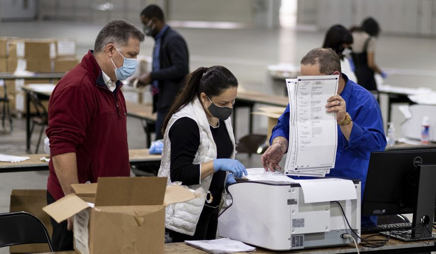 Workers scan ballots as the Fulton County presidential recount gets underway Wednesday morning, Nov. 25, 2020, at the Georgia World Congress Center in Atlanta. (AP Photo/Ben Gray) ** FILE **