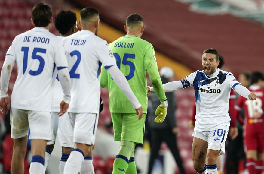 Atalanta's Papu Gomez, right, celebrates with teammates following the Champions League group D soccer match between Liverpool and Atalanta at Anfield stadium in Liverpool, England, Wednesday, Nov. 25, 2020. (AP Photo/Jon Super, Pool)