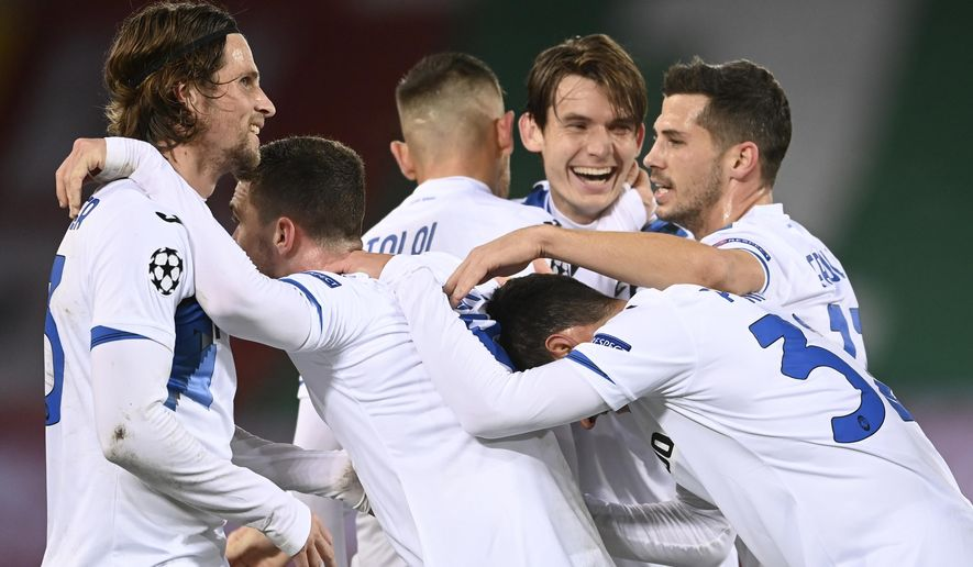 Atalanta players celebrate after scoring their second goal during the Champions League group D soccer match between Liverpool and Atalanta at Anfield stadium in Liverpool, England, Wednesday, Nov. 25, 2020. (Laurence Griffiths/Pool via AP)