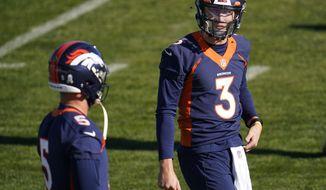 Denver Broncos quarterback Drew Lock, right, confers with quarterback Riley Neal during NFL football practice Wednesday, Nov. 25, 2020, in Englewood, Colo. (AP Photo/David Zalubowski)