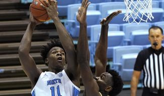 North Carolina forward Day'Ron Sharpe (11) shoots over College of Charleston center Osinachi Smart (33) during the first half of an NCAA college basketball game in Chapel Hill, N.C., Wednesday, Nov. 25, 2020. (AP Photo/Gerry Broome)