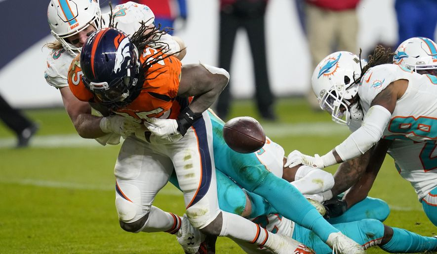 Miami Dolphins outside linebacker Andrew Van Ginkel (43) forces Denver Broncos running back Melvin Gordon (25) to fumble the football during the second half of an NFL football game, Sunday, Nov. 22, 2020, in Denver. (AP Photo/David Zalubowski)