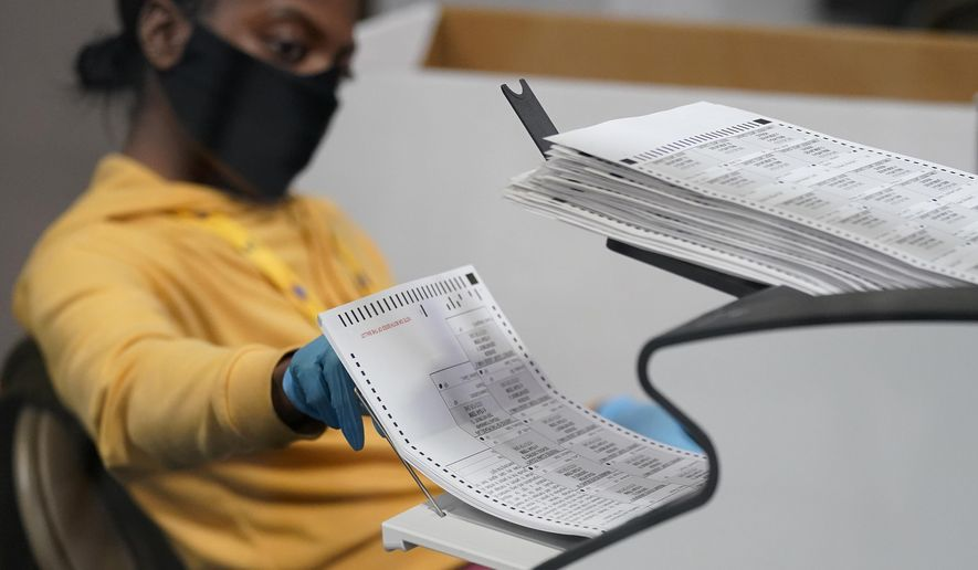 A county election worker scans mail-in ballots at a tabulating area at the Clark County Election Department in Las Vegas, Nov. 5, 2020. (AP Photo/John Locher) ** FILE **