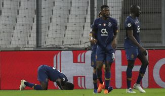 Porto's Zaidu Sanusi, left, leans to the pitch after scoring his side opening goal during the Champions League group C soccer match between Olympique Marseille and FC Porto at the Velodrome stadium in Marseille, southern France, Wednesday, Nov.25, 2020. (AP Photo/Daniel Cole)