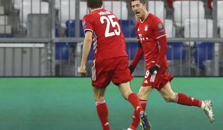Bayern's Robert Lewandowski, right, celebrates with Bayern's Thomas Mueller after scoring his sides first goal during the Champions League Group A soccer match between Bayern Munich and RB Salzburg at the Allianz Arena in Munich, Czech Republic, Wednesday, Nov. 25, 2020. (AP Photo/Matthias Schrader)