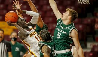 Minnesota guard Both Gach (11) goes to the basket and is fouled by Green Bay guard Josh Jefferson (0) and as guard Lucas Stieber (5) also defends during the first half of an NCAA college basketball game Wednesday, Nov. 25, 2020, in Minneapolis. (AP Photo/Bruce Kluckhohn)