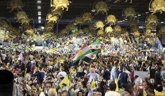 FILE- In this Friday June 27, 2014 file photo, thousands of exiled Iranians gathered in Villepinte, north of Paris, to listen to the speech of Maryam Rajavi, the leader of the National Council of Resistance of Iran. Four people are going on trial in the Belgian city of Antwerp on Friday Nov. 27, 2020, accused of planning to bomb a rally of Iranian opposition supporters. The plot was thwarted by a cross-border intelligence operation that led to the arrest of a couple in Brussels. (AP Photo/Rermy de la Mauviniere, File)