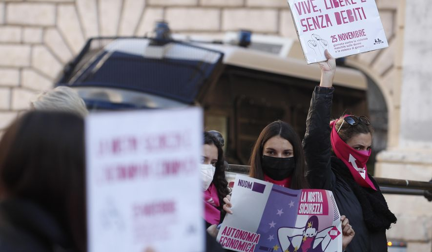 """A woman show a banner reading """"alive, free and without debts"""" during a demonstration on the occasion of International Day for the Elimination of Violence against Women, in Rome, Wednesday, Nov. 25, 2020. (AP Photo/Alessandra Tarantino)"""
