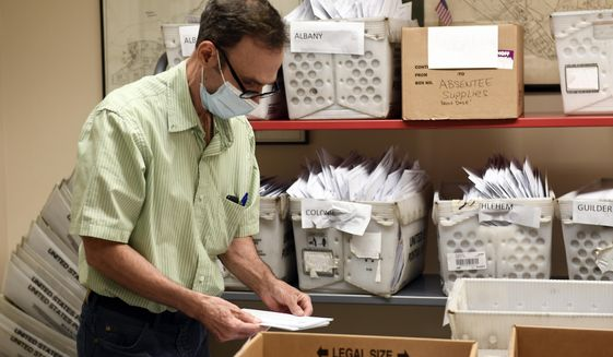 FILE - In this Oct. 14, 2020, file photo, Frank Bongiorno sorts Absentee Ballots at the Albany County Board of Elections building in Albany, N.Y. New York may permanently expand voting by mail, something it tried on a wide scale for the first time in 2020, while also trying to reform its molasses-slow and opaque process for counting absentee ballots. (AP Photo/Hans Pennink, File)