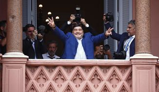 FILE - In this Dec. 26, 2019 file photo, former soccer great Diego Maradona flashes victory signs to fans below at the Casa Rosada government house after meeting with Argentine President Alberto Fernandez in Buenos Aires, Argentina. Decades ago, Maradona held up his team's soccer trophy at this spot on the balcony after winning the World Cup in Mexico in 1986. The Argentine soccer great who was among the best players ever and who led his country to the 1986 World Cup title before later struggling with cocaine use and obesity, died from a heart attack on Wednesday, Nov. 25, 2020, at his home in Buenos Aires. He was 60. (AP Photo/Marcos Brindicci, File)