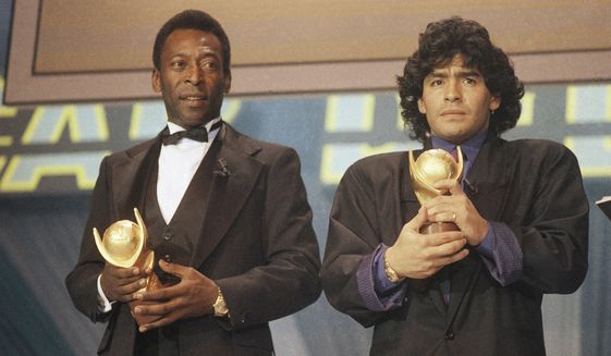 """In this March 1987 file photo, Pele, left, and Maradona hold """"Sports Oscar"""" trophies in Milan, Rome. The Argentine soccer great who was among the best players ever and who led his country to the 1986 World Cup title before later struggling with cocaine use and obesity, died from a heart attack on Wednesday, Nov. 25, 2020, at his home in Buenos Aires. He was 60. (AP Photo/File)  **FILE**"""