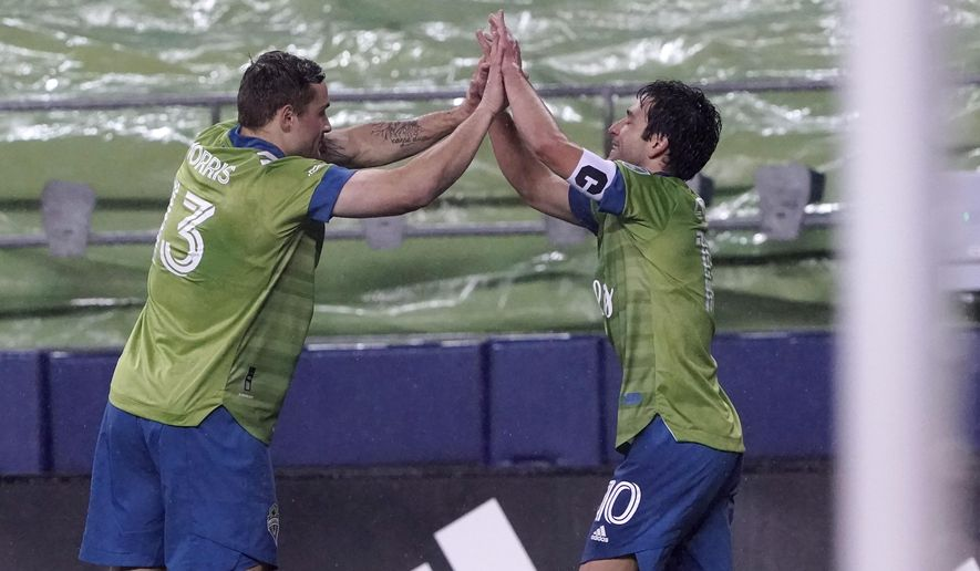 Seattle Sounders' Nicolas Lodeiro (10) is congratulated on his goal by Jordan Morris (13), who had an assist, during the first half of an MLS playoff soccer match against Los Angeles FC on Tuesday, Nov. 24, 2020, in Seattle. (AP Photo/Ted S. Warren)