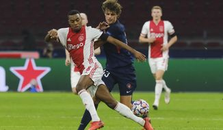 Ajax's Ryan Gravenberch, left, and Midtjylland's Nicolas Madsen vie for the ball during the group D Champions League soccer match between Ajax and Midtjylland at the Johan Cruyff ArenA in Amsterdam, Netherlands, Wednesday, Nov. 25, 2020. (AP Photo/Patrick Post)