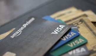 FILE - This Aug. 11, 2019 file photo shows credit cards in New Orleans.  If you want to help nonprofits this holiday season consider donating your unused hotel points, airline miles or credit card rewards to charity.  (AP Photo/Jenny Kane, file)