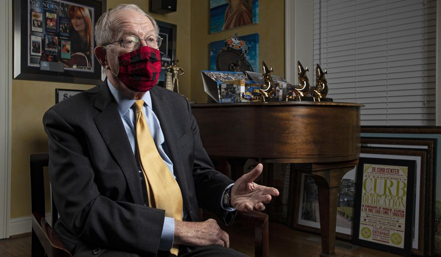 Sen. Lamar Alexander, R-Tenn., speaks from behind a face mask during an interview Friday, Nov. 20, 2020, in Nashville, Tenn. (AP Photo/Wade Payne)