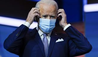 FILE - In this Nov. 24, 2020, file photo President-elect Joe Biden puts on his face mask after introducing nominees and appointees to key national security and foreign policy posts at The Queen theater in Wilmington, Del. Congress is bracing for Biden to move beyond the Trump administration's state-by-state approach to the COVID-19 crisis and build out a national strategy to fight the pandemic and distribute the eventual vaccine.(AP Photo/Carolyn Kaster, File)