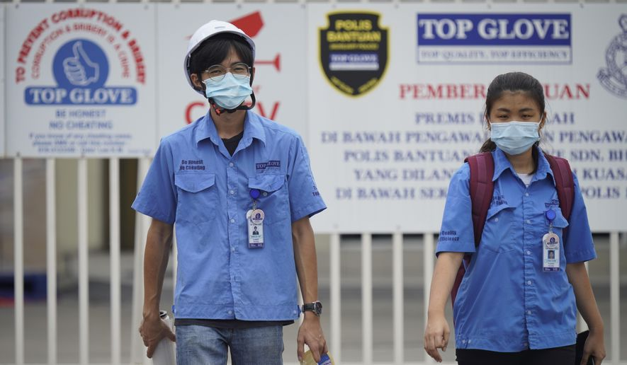 Workers from Top Glove walk out from Top Glove factory in Shah Alam, Malaysia, Wednesday, Nov. 25, 2020. Malaysia's Top Glove Corp., the world's largest maker of rubber gloves, says it expects a two to four-week delay in deliveries after more than 2,000 workers at its factories were infected by the coronavirus, raising the possibility of supply disruptions during the pandemic. (AP Photo/Vincent Thian)