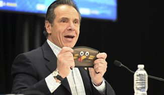 In this provided by the State of New York, New York Gov. Andrew Cuomo holds up a new Thanksgiving-themed face mask during his daily coronavirus briefing at the Wyandanch-Wheatley Heights Ambulance Corp. Headquarters in Wyandanch, N.Y. After disclosing that he will no longer be celebrating Thanksgiving with his 89-year-old mother in-person, Cuomo asked New Yorkers to abandon plans for in-person Thanksgiving festivities. (Kevin P. Coughlin/State of New York via AP)