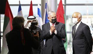Israeli Prime Minister Benjamin Netanyahu, center and flydubai CEO Ghaith Al Ghaith, right, attend a welcoming ceremony for the first flydubai commercial flight to arrive at Ben-Gurion International Airport, Israel, Thursday, Nov. 26, 2020. (Emil Salman/Pool via AP)
