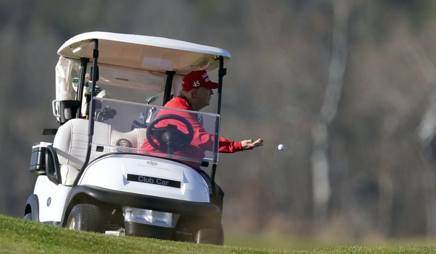 President Donald Trump tosses a golf ball as he plays golf at Trump National Golf Club, on Thanksgiving, Thursday, Nov. 26, 2020, in Sterling, Va. (AP Photo/Alex Brandon)