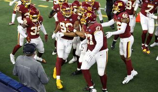 Washington Football Team's Montez Sweat (90) is congratulated by teammates after returning a Dallas Cowboys quarterback Andy Dalton interception for a touchdown in the second half of an NFL football game in Arlington, Texas, Thursday, Nov. 26, 2020. (AP Photo/Roger Steinman)