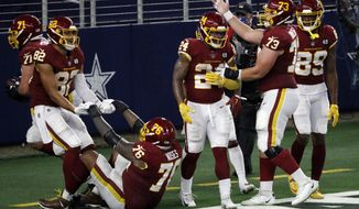 Washington Football Team's Antonio Gibson (24) is congratulated by Chase Roullier (73) and others after his touchdown run in the second half of an NFL football game against the Dallas Cowboys in Arlington, Texas, Thursday, Nov. 26, 2020. (AP Photo/Roger Steinman)