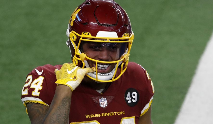 Washington Football Team running back Antonio Gibson (24) points to his mouth as he celebrates his touchdown in the second half of an NFL football game against the Dallas Cowboys in Arlington, Texas, Thursday, Nov. 26, 2020. (AP Photo/Roger Steinman)