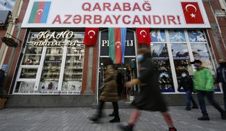 "People walk past a poster reading ""Karabakh is Azerbaijan"" in Ganja, Azerbaijan's second largest city, near the border with Armenia, Azerbaijan, Thursday, Nov. 26, 2020. Azerbaijan's President Ilham Aliyev has vowed to rebuild and revive the Kalbajar region, which Armenian forces ceded in a truce that ended six weeks of intense fighting over Nagorno-Karabakh. (AP Photo/Emrah Gurel)"